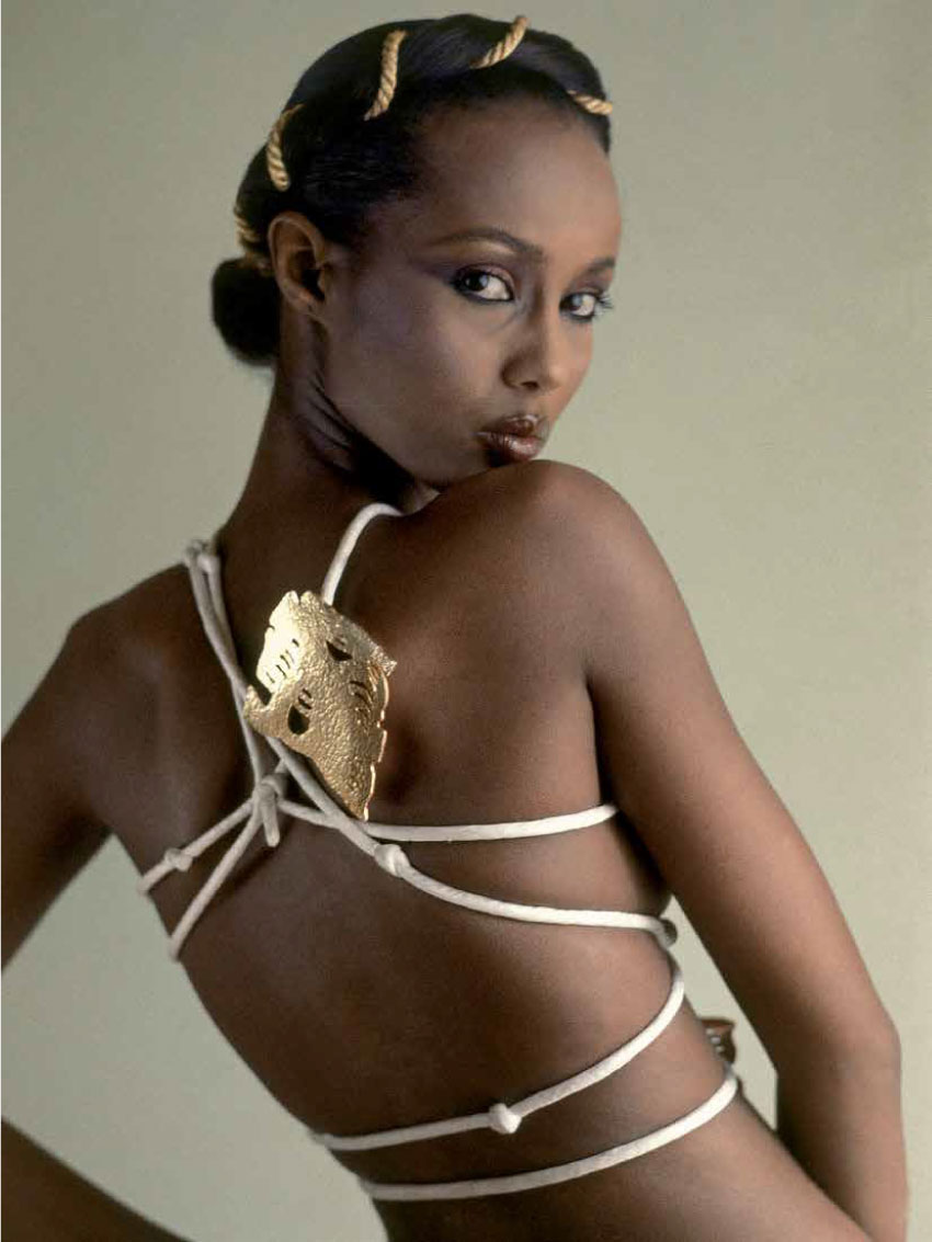 Model, Iman, with body wrapping of silk cording anchored with a huge golden jewel.